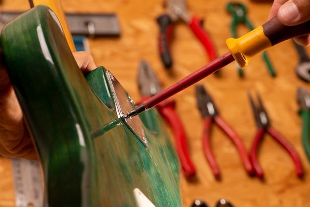 Gitarrenbauer arbeitet an der reparatur einer gitarre