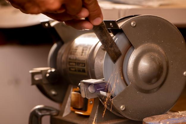 Gitarrenbauer mit schleifmaschine zur herstellung von metallteilen