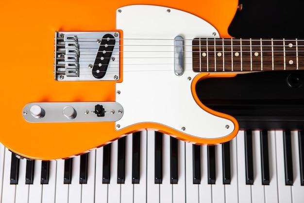 Gitarrendeck vor klaviertasten, draufsicht der nahaufnahme. konzept