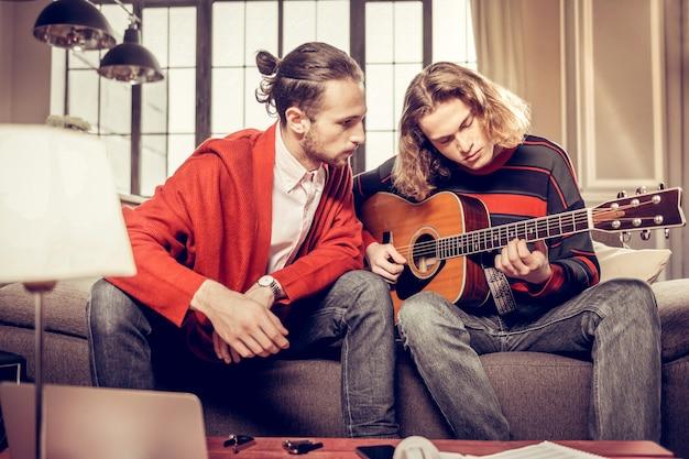 Gitarrenlehrer. bärtiger dunkelhaariger gitarrenlehrer hört seinem schüler zu, nachdem er etwas geübt hat