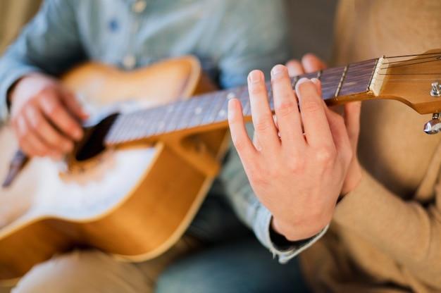 Gitarrenlehrer zeigt dem schüler, wie man das instrument spielt