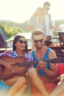 Gitarrenspaß. fröhlicher junger mann, der seiner freundin beibringt, gitarre zu spielen, während zwei leute im hintergrund grillen