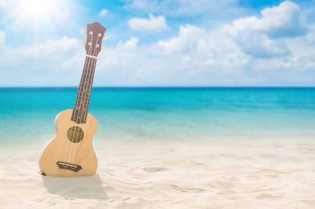 Gitarrenukulele auf sandstrand mit heller sonne