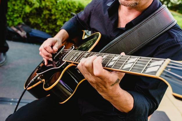 Gitarrist, der draußen seine gitarre spielt