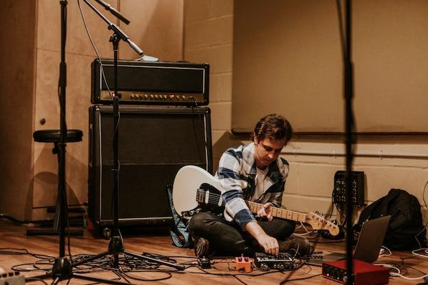 Gitarrist, der rockmusik im studio aufnimmt, auf dem boden sitzend