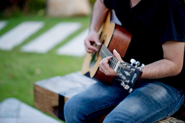 Gitarrist, ein junger mann, der eine gitarre spielt, während er in einem natürlichen garten sitzt