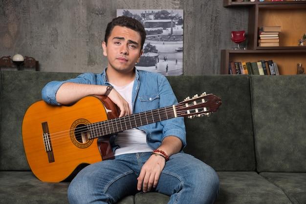 Gitarrist hält eine schöne gitarre und sitzt auf dem sofa. hochwertiges foto