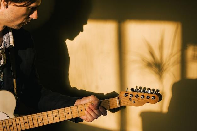 Gitarrist mit e-gitarre, die zu hause spielt