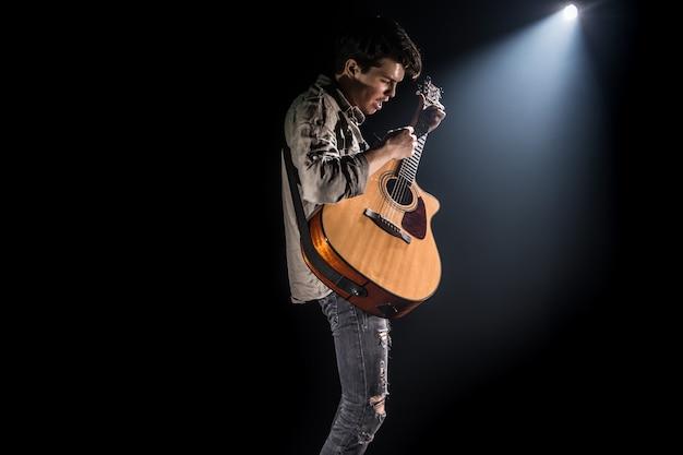 Gitarrist, musik. ein junger mann spielt eine akustikgitarre auf einem schwarzen isolierten hintergrund. spitzlicht