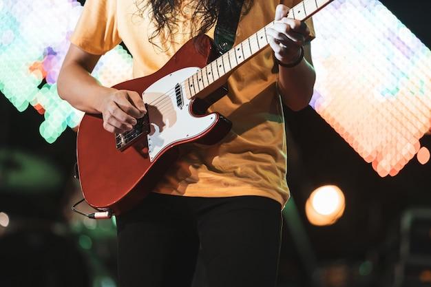 Gitarrist spielt elektrizitätsgitarre auf konzertbühne. eingabe- und musikkonzept.