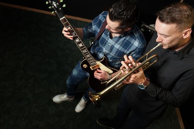 Gitarrist und trompetenspieler im studio