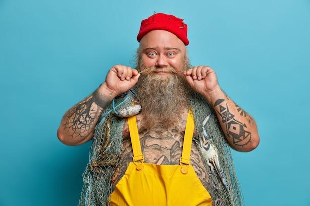 Glad fisherman curls schnurrbart, hat einen dicken bart, trägt ein fischernetz auf den schultern, verbringt freizeit für hobby und seele, trägt einen roten hut und einen overall, hat einen tätowierten körper