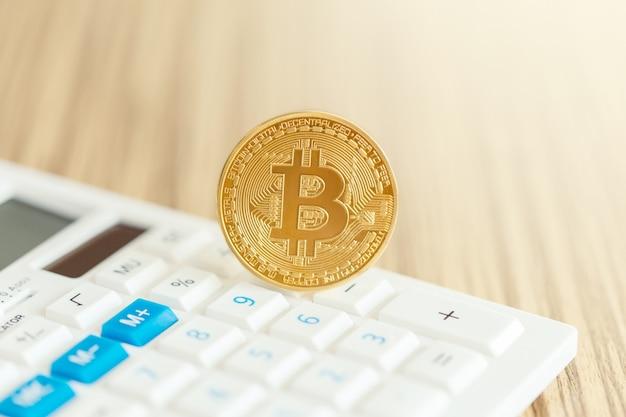 Glänzend goldenes bitcoin auf dem taschenrechner