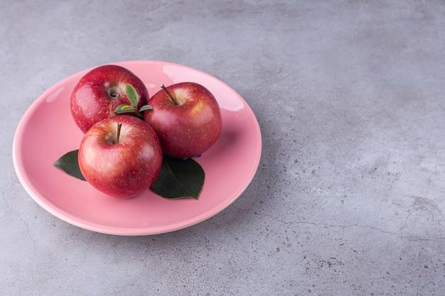 Glänzend rote äpfel mit grünen blättern auf stein.