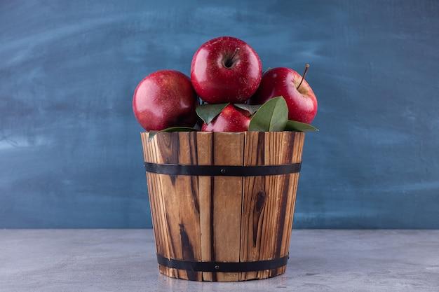 Glänzend rote äpfel mit grünen blättern auf steinoberfläche.