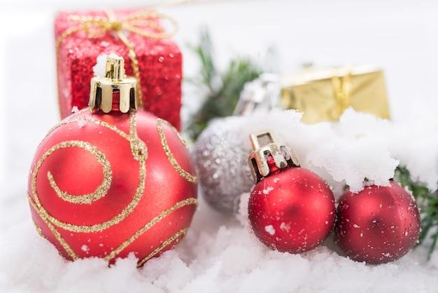Glänzend rote weihnachtskugeln und geschenkboxdekoration über schnee