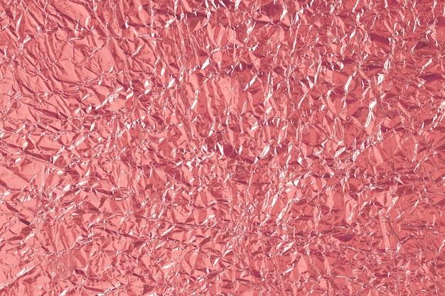 Glänzende beschaffenheit der roségoldfolie, abstraktes rotes packpapier