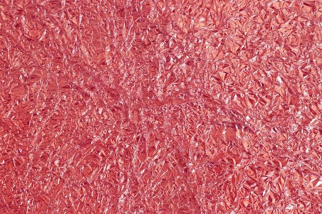 Glänzende beschaffenheit der rosen-goldfolie, abstraktes rotes packpapier für hintergrund und designkunstwerk.