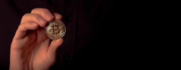Glänzende bitcoin btc goldene münze in der männlichen hand über schwarzem hintergrund. bit-kryptowährungsbanner mit platz für text.