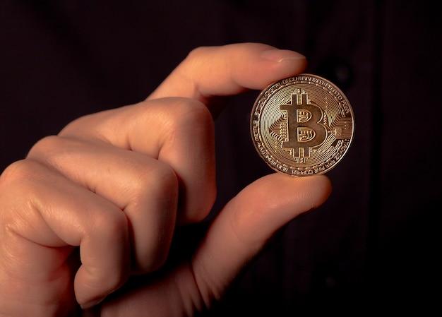 Glänzende bitcoin btc goldene münze in männlicher hand über schwarzem hintergrund bit kryptowährung