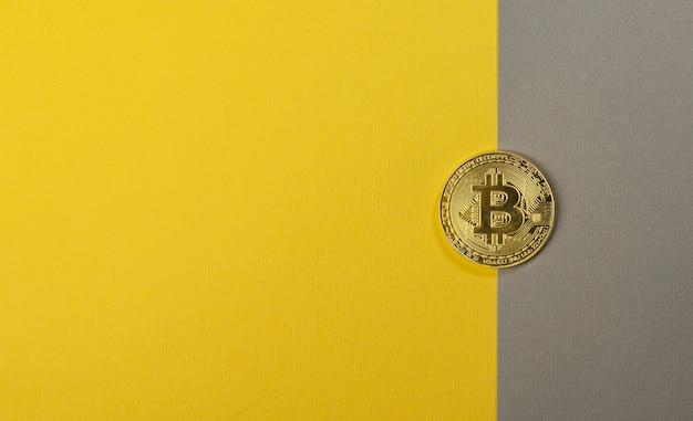 Glänzende bitcoin-münze auf trendigem gelbem und grauem hintergrund mit kopienraum