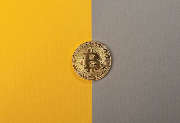 Glänzende bitcoin-münze auf trendigem gelbem und grauem tisch.