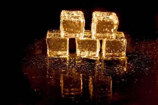 Glänzende eiswürfel auf goldenem licht.