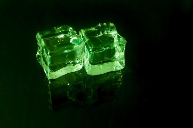 Glänzende eiswürfel auf grünem licht.