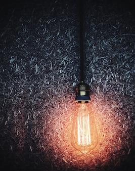 Glänzende glühlampe, die über dunklem bretthintergrund der hölzernen masse hängt
