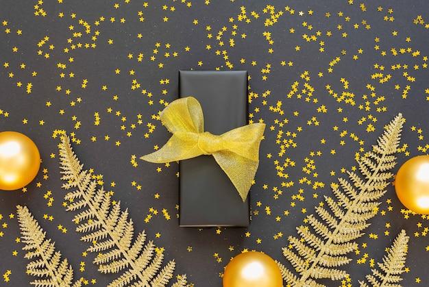 Glänzende goldene farnblätter und geschenkbox mit weihnachtskugeln auf schwarzem hintergrund mit glitzernden goldenen sternen, flache lage, draufsicht, kopierraum