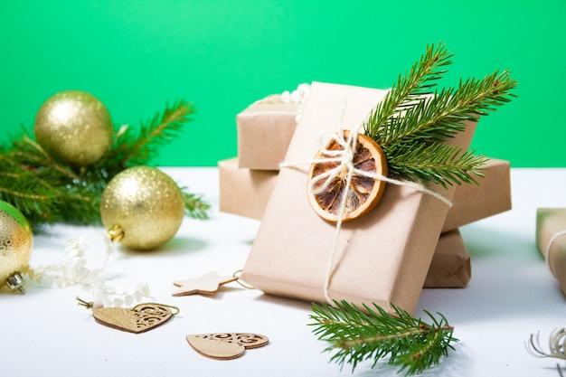 Glänzende goldkugeln für den weihnachtsbaum und mehrere geschenkboxen, die in kraftpapier eingewickelt und mit getrockneten orangen- und fichtenzweigen auf grünem hintergrund dekoriert sind, öko-weihnachtskonzept