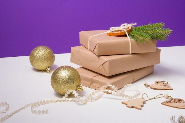 Glänzende goldkugeln für den weihnachtsbaum und mehrere geschenkboxen, die in kraftpapier verpackt und mit natürlichen materialien auf violettem hintergrund dekoriert sind, öko-weihnachtskonzept