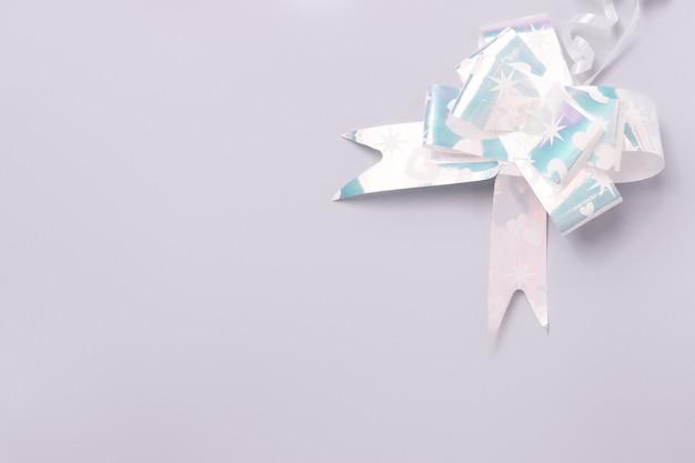 Glänzende graue schleife für geschenkverpackung auf ultimativem grauem hintergrund mit leerer werbefläche.