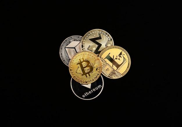 Glänzende kryptowährungsmünzen häufen sich auf schwarzem hintergrund, draufsicht auf bitcoin, monero, litecoin, ethereum.