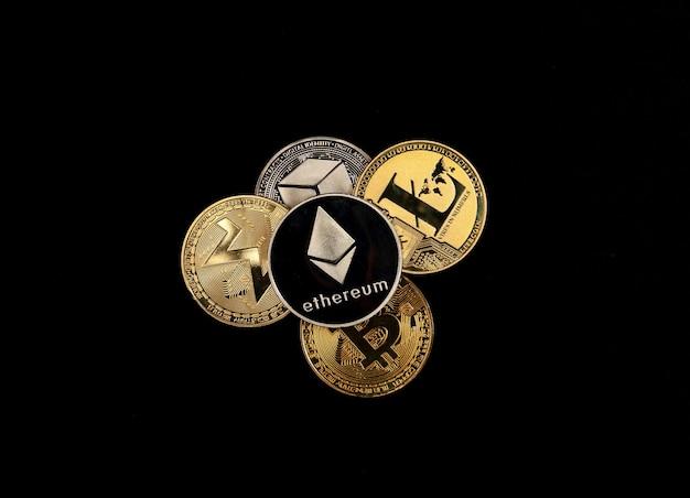 Glänzende kryptowährungsmünzen stapeln sich auf schwarzem hintergrund, draufsicht auf ethereum, bitcoin, monero, litecoin.