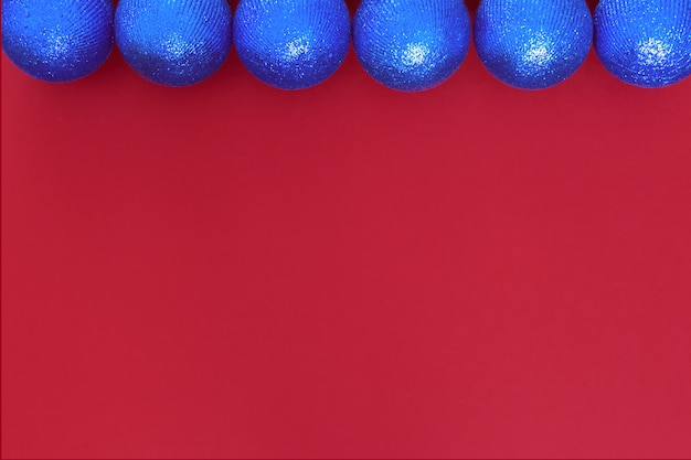 Glänzende kugeln der blauen kugeln-weihnachtsfeiertage auf rotem papierhintergrund zur verwendung als texturgruß-feiertagsdekoration.