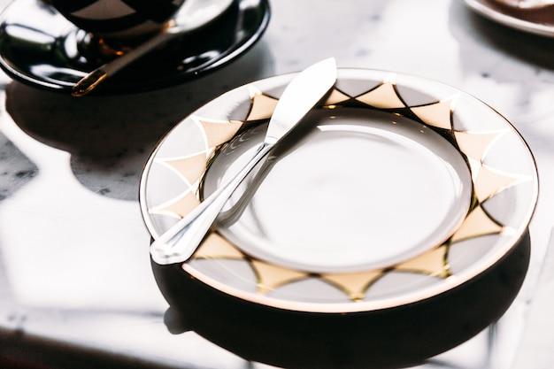 Glänzende leere platte des goldenen und silbernen musters mit buttermesser auf marmortischplatte.