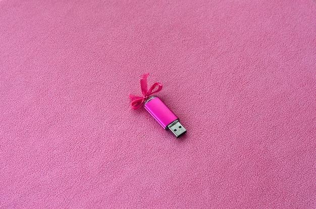 Glänzende rosa usb-flash-speicherkarte mit rosa schleife
