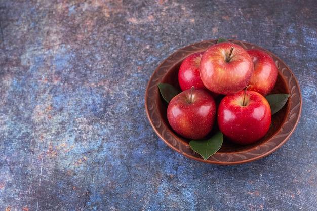 Glänzende rote äpfel mit grünen blättern auf steinhintergrund.