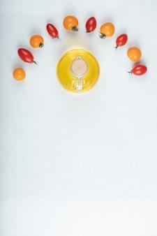 Glänzende rote und gelbe tomaten auf weißem hintergrund mit flasche öl. hochwertiges foto