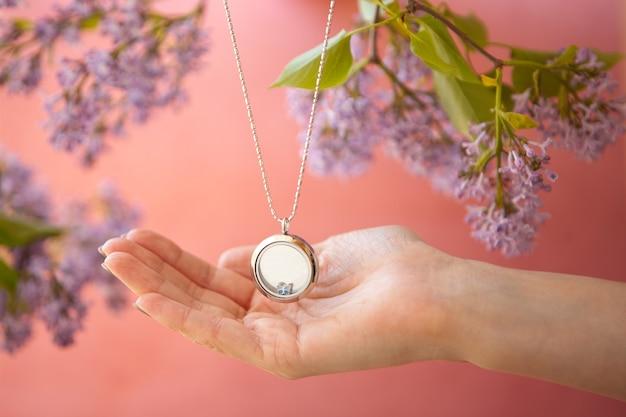 Glänzende silberne halskette für die dame an den händen der frau in der nähe von lila blumen luxus-silberschmuckketten