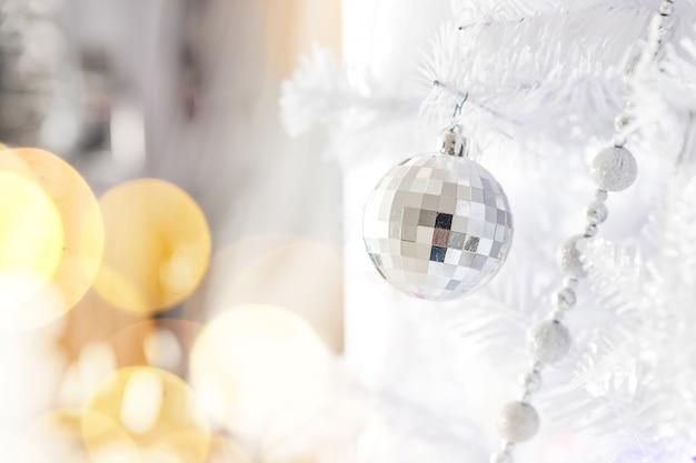 Glänzende silberne weihnachtskugel auf einem weihnachtsbaum auf silber