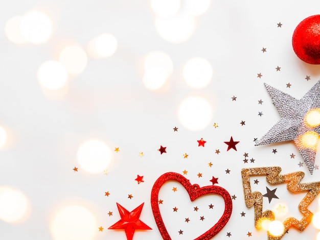 Glänzende sterne, kugeln, schneeflocken, herz, konfetti und glühbirnen