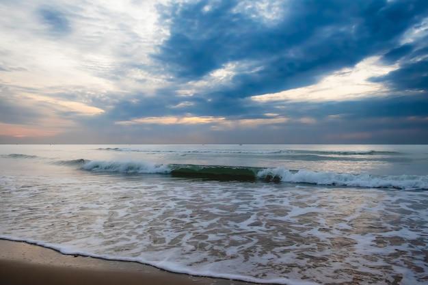 Glänzende tropische seewelle auf strandsand mit bewölktem himmel