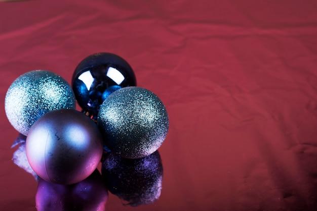 Glänzende weihnachtskugeln, die auf burgunder-gewebe liegen