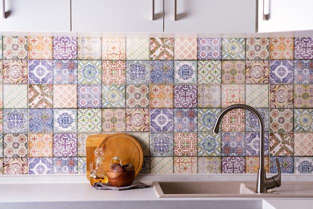 Glänzender edelstahlhahn mit chromwasserhahn, steinwanne und hölzernen schüsseln mit olivenoliven auf einer wand der farbigen alten fliesen. küche innenraum