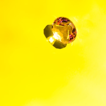 Glänzender funkelnder diamant mit schatten auf gelbem hintergrund