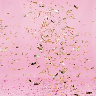 Glänzender goldener confetti, der auf rosa hintergrund fällt