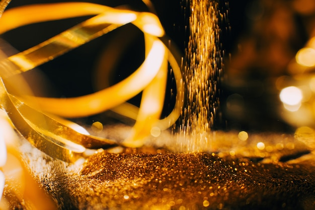 Glänzender goldglitter wasserfallhintergrund. konzept für nagelkunst und make-up-materialien