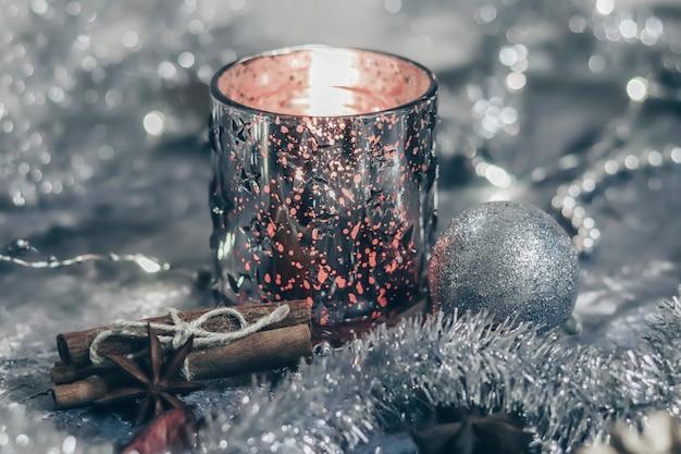 Glänzender kerzenhalter mit einer brennenden kerze auf einem silbernen hintergrund mit festlichen dekorationen. flache karte